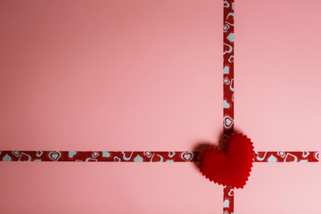 A gift for Valentine's Day or a wedding. Pink packaging with ribbons and red velvet heart with copy space in soft focus