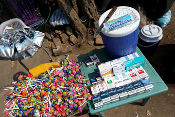 Medicines are seen next to packets of cigarettes and lollipops in a street, in Villa del Rosario