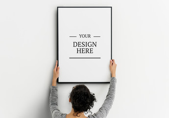 Person Hanging Frame on Wall Mockup