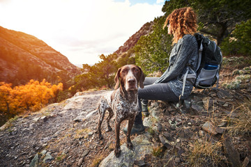 a young woman and her dog at the top of a mountain