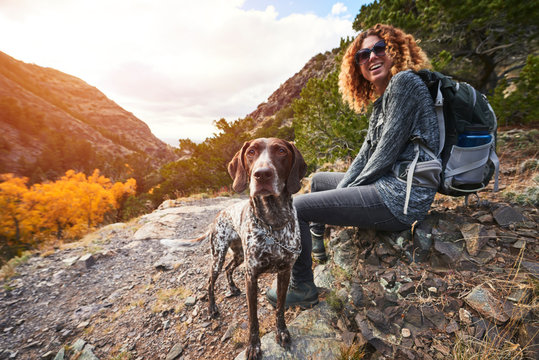 a young woman and her dog hiking to the top of a mountain