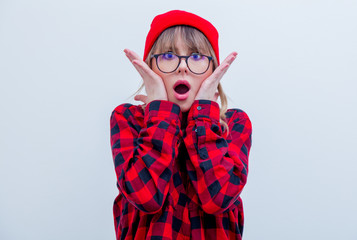 Young surprised woman in red shirt and hat