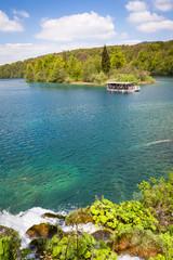 Park boat on Kozjak lake against green forests, Plitvice Lakes National Park, Croatia