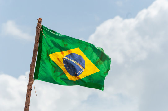 Brazilian flag is waving at a beautiful and peaceful blue sky at Amazonas river.