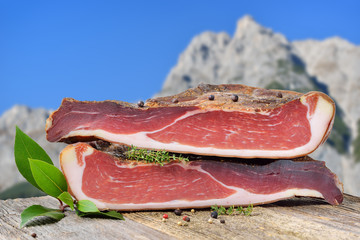 Südtiroler Speck auf einem Holztisch vor Bergen in den Alpen – Typical South Tyrolean bacon divided into two halfes lying on a rustic table in front of mountains of the alps
