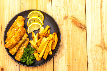 Fish and chips in black plate on wooden table. Traditional British food, top view