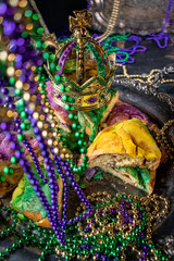 king cake with crown surrounded by mardi gras beads