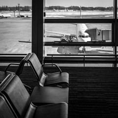 View from the airport terminal to the passenger aircraft with a boarding gate at the airport apron. Airplane travel