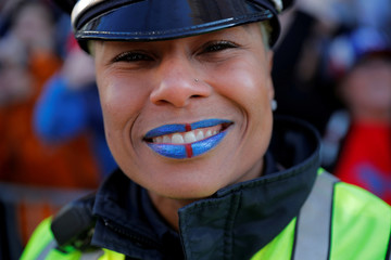 A Boston Police officer has her lips painted the colors of the New England Patriots during their victory parade in Boston