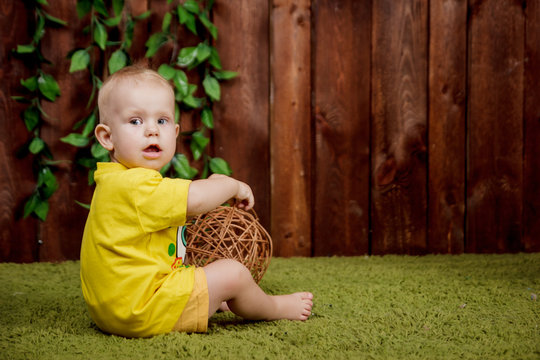 Portrait of a cute little european girl sitting in the yellow shirt on a green carpet in the studio with the brown background of wooden boards
