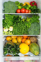 Opened fridge full of fresh colorful fruits and vegetables