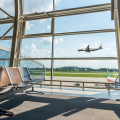 View from the airport lounge to landing plane, passenger aircraft in the sky. Airplane travel concept. Summer vacation