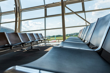 Interior inside airport terminal. Lounge with chairs in waiting departure area. Summer vacation. Airplane travel concept