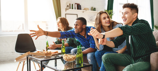 group of happy friends fans watching a match on tv with beer and pizza at home.