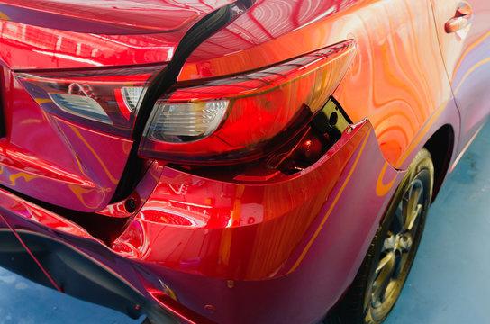 Rear bumper dented red car