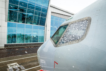 Airliner near airport terminal. Aircraft at heavy snow. Plane in snow at airport. Bad weather, snow blizzard at airport