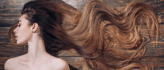 Poster Kapsalon Woman with beautiful long hair on wooden background. Long hair. Trendy haircuts. Beauty hair Salon.
