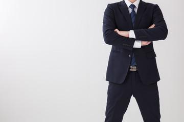 白背景でスーツの男性が上半身で腕を組んで怒っている場面