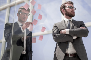 employees standing near a transparent office wall