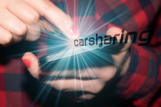 Eine Frau informiert sich am Smartphone über das Carsharing