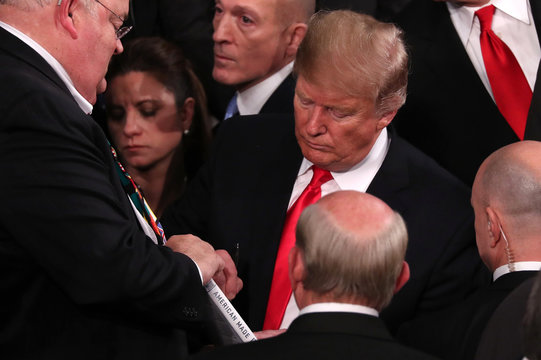 U.S. President Trump signs a book after delivering his second State of the Union address to a joint session of the U.S. Congress in Washington