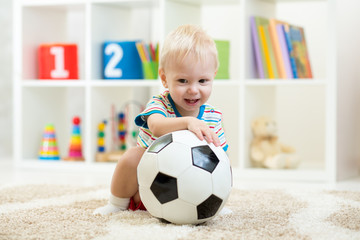Nursery child boy playing with soccer-ball at home or daycare