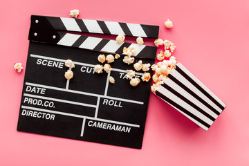 Film watching concept. Clapperboard and popcorn on pink background top view