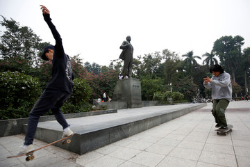 Boys ride the skateboards in front of an statue of Russian revolutionary Vladimir Lenin in a park in Hanoi
