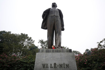 A girl plays on the statue of Russian revolutionary Vladimir Lenin in a park in Hanoi