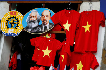 Images of the revolutionary icons Karl Marx and Vladimir Lenin are seen next to t-shirts at a shop in Hanoi