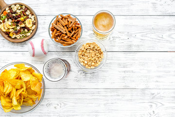 Snacks for watching american football on TV. Watching sports. Chips, nuts, rusks near beer and ball on white wooden background top view copy space