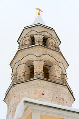 the unrestored bell tower on the territory of the old orthodoxal monastery in the small Russian town Torzhok in winter