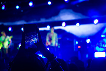 Woman taking a photo with phone at music event