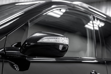 Close-up of the mirror of the car body  black sedan on the street parking in the snow.
