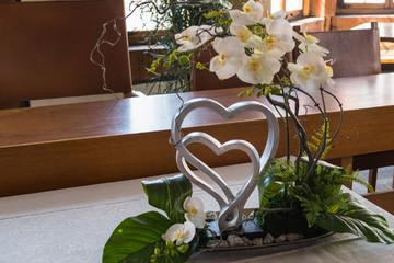Orchideen-Gesteck mit verflochtenen Herzen
