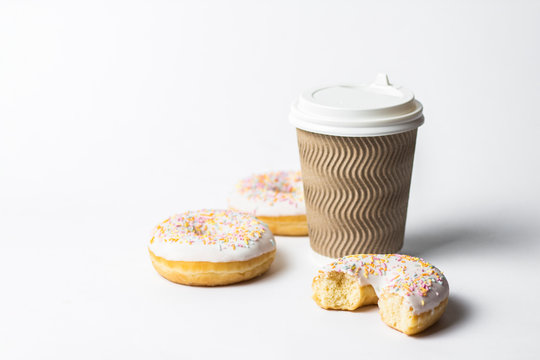 A paper cup with a lid, coffee or tea to go and fresh tasty donuts and sweet multicolored decorative candies on a white background. Bakery concept, fresh pastries, delicious breakfast, fast food.