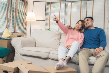 Sweet happy young Asian couple moving clothes and many objects from old home to their new home and relax on sofa in living room at their home. Lifestyle couple move new home.