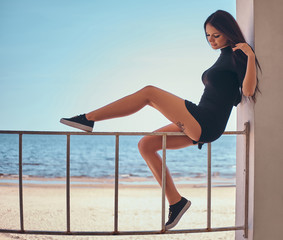 Young beautiful girl with a tattoo on her leg sitting on the railing against the beautiful sea coast