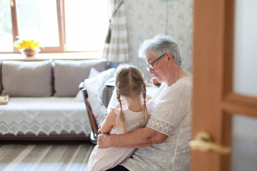 Grandmother is hugging granddaughter in cozy home living room. Kind senior woman is telling story or fairy tale to cute little child girl. Kid is enjoying warm hands, care, support and consolation.