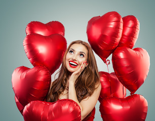 Beautiful woman holds red heart balloons. Surprise, valentines people and Valentine's day concept . Expressive facial expressions