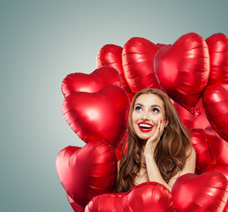 Young woman with balloons red heart. Surprised girl with red lips makeup, curly hair and cute smile looking up. Surprise, sale and Valentine's day concept . Expressive facial expressions