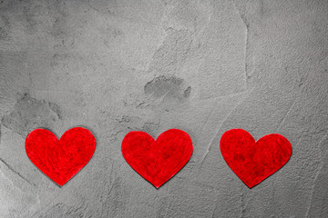Three Red paper hearts on gray wall with copy space