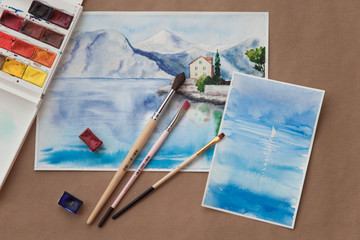 Watercolor postcards with with blue sea, sailboat and yachting among brushes and paints. Hand drawn pictures with sailing, seaside summer landscapes. Artistic flat lay. Romantic female leisure, hobby.