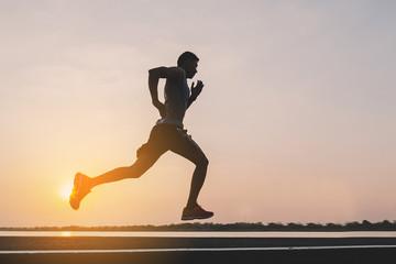 Fototapeta young man runner running on running road in city park obraz