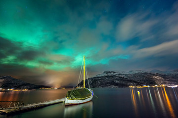 Northern lights in the Norwegian fjord and the yacht