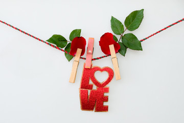 Red word LOVE  and rose on rope with clothespins, on a white  background