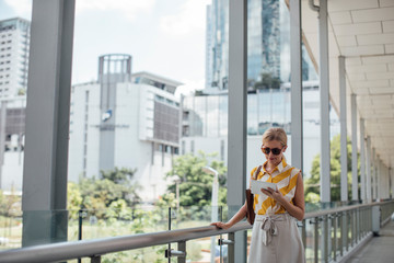 Pretty elegant Caucasian businesswoman standing at the city and holding a tablet.