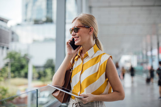 Pretty elegant businesswoman holding a tablet and talking on a cell phone.