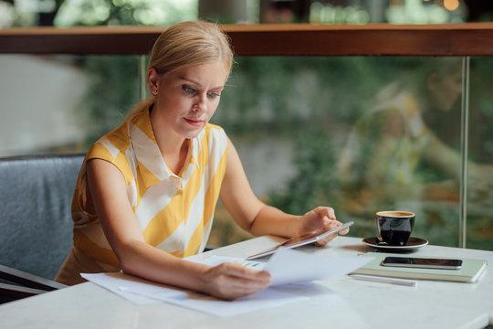 Pretty Caucasian serious businesswoman reading a document.