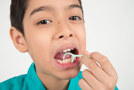 Little boy using dental floss to clean tooth